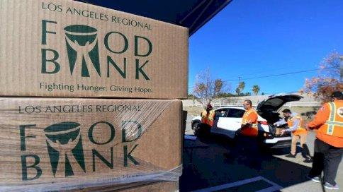 متطوعون في أحد بنوك الطعام في لوس انجلس يوزعون صناديق في سيلمالا في كاليفورنيا الخميس