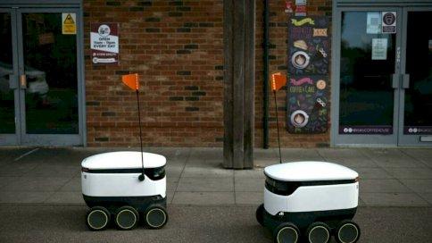 روبوتات صغيرة تتنقل على عجلات ست مع صناديق بيضاء أنيقة في شوارع بريطانيا.