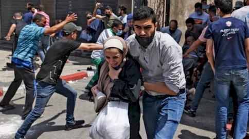 فلسطينيون يخلون بناءً في غزة قصفه الطيران الإسرائيلي الثلاثاء