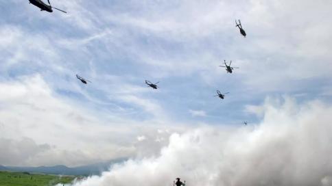 طوافات عسكرية يابانية تحلق فوق عربات مدرعة خلال تدريبات سنوية في منطقة شيزووكا